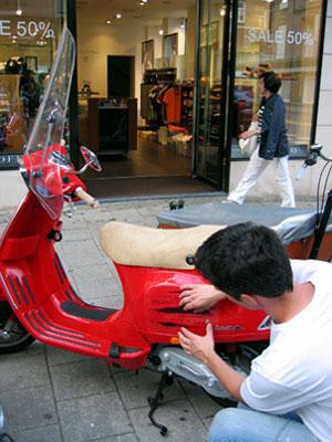 Приклеивание наклейки на скутере